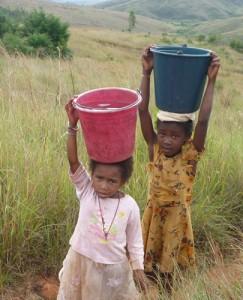 Fillettes malgaches portants des seaux d'eau